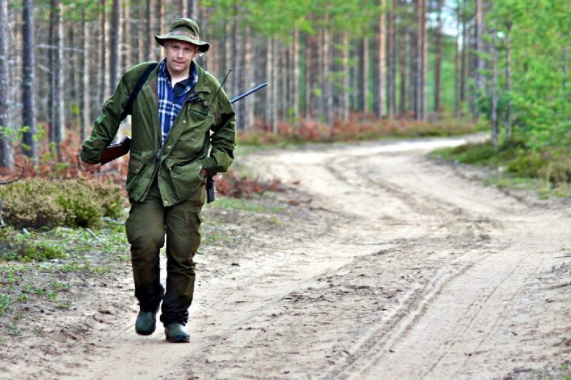 En man kommer och går längs en skogsväg, klädd för jakt.