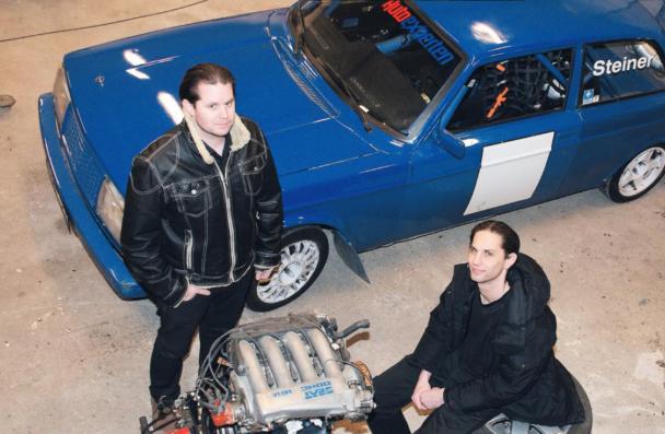 Daniel och Sebastian Steiner i verkstaden, framför en blå Volvo.