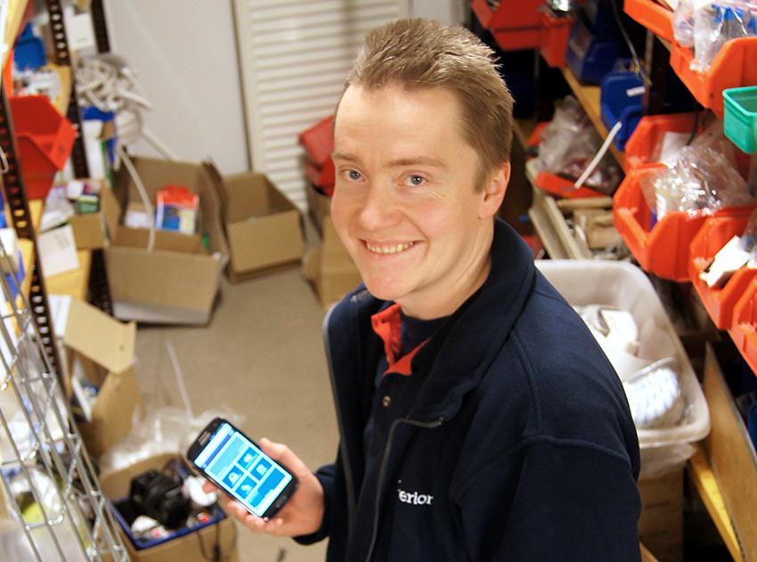 """Telefonen har blivit ett bra hjälpmedel i vardagen, menar Emil Rabe serviceinstallatör på Caverion i Borås, som skriver upp vad han plockar med sig från lagret. Sedan några månader sköter han allat """"pappersarbete"""" med hjälp av telefonen och ett specialsytt program. Foto: Jan-Erik Johansson"""