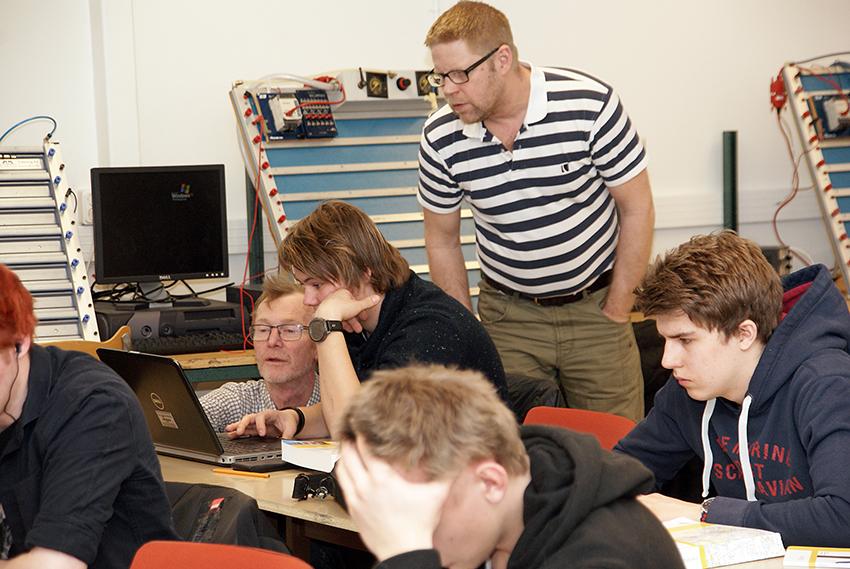 Läraren Peter Mårtensson, sittande, och kontrollanten Patrik Söderqvist, stående, guidar en av eleverna när provet ska starta. Foto: Per Eklund