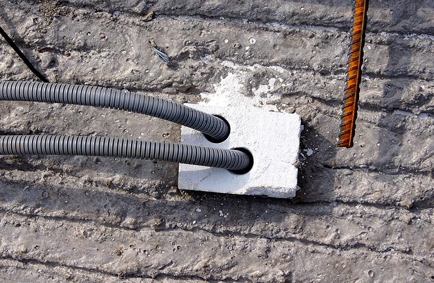 Klossar av gips ligger ingjutna i filigranvalvet för nedföringar till mellanväggar. Mattias Edling borrar så många hål han behöver och skickar ned färdigdragen slang. FOTO: JAN-ERIK JOHANSSON
