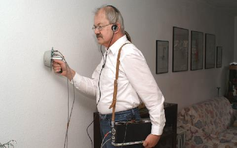 En person med hörlurar arbetar med avlyssning vid en vägg