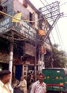 En stadsvy där massor av elledningar hänger fritt mellan husen
