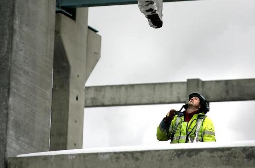 En person i gul jacka och hjälm tittar upp mot en bjälke på ett bygge