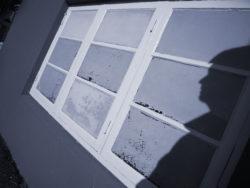 En skugga av en person mot en husvägg med ett stort fönster.