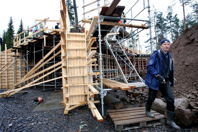 En person som går invid en byggställning.