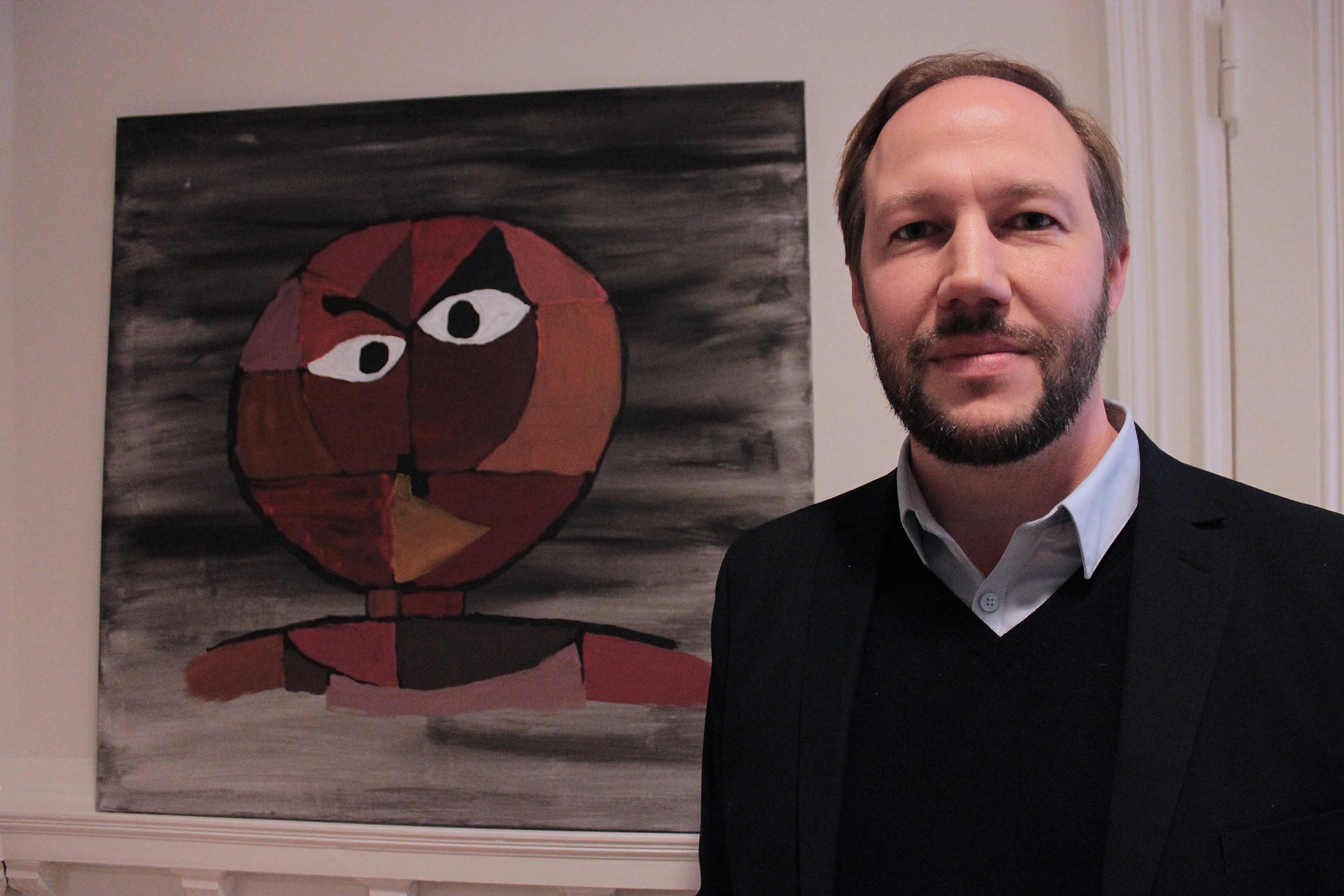 Bilden föreställer en man med brunt, kort hår och skägg, klädd i en svart tröja med en skjorta under. På väggen bakom honom hänger ett abstrakt porträtt av en människa med runt huvud.