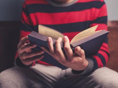 En ung person sitter och läser en bok