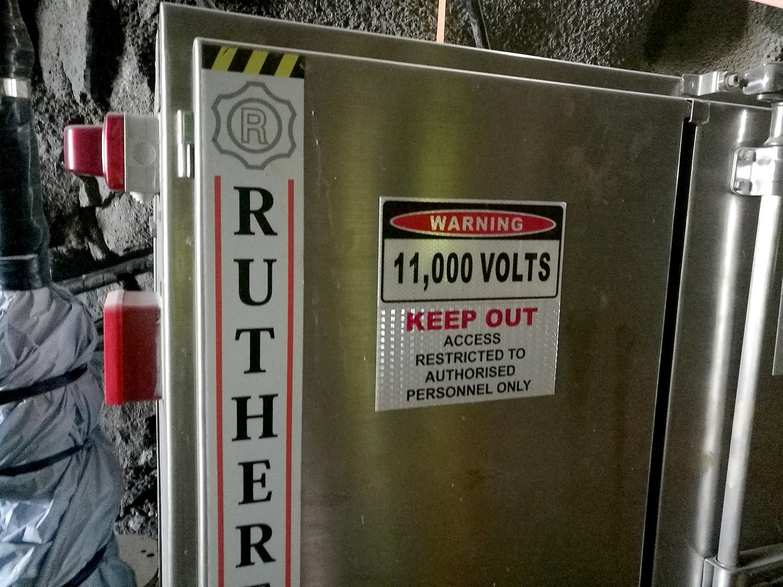 Bilden föreställer ett grått metallskåp med en varningsskylt på. Warning, 11000 volts, keep out, access restricted tp authorised personnel only, står det på skylten.