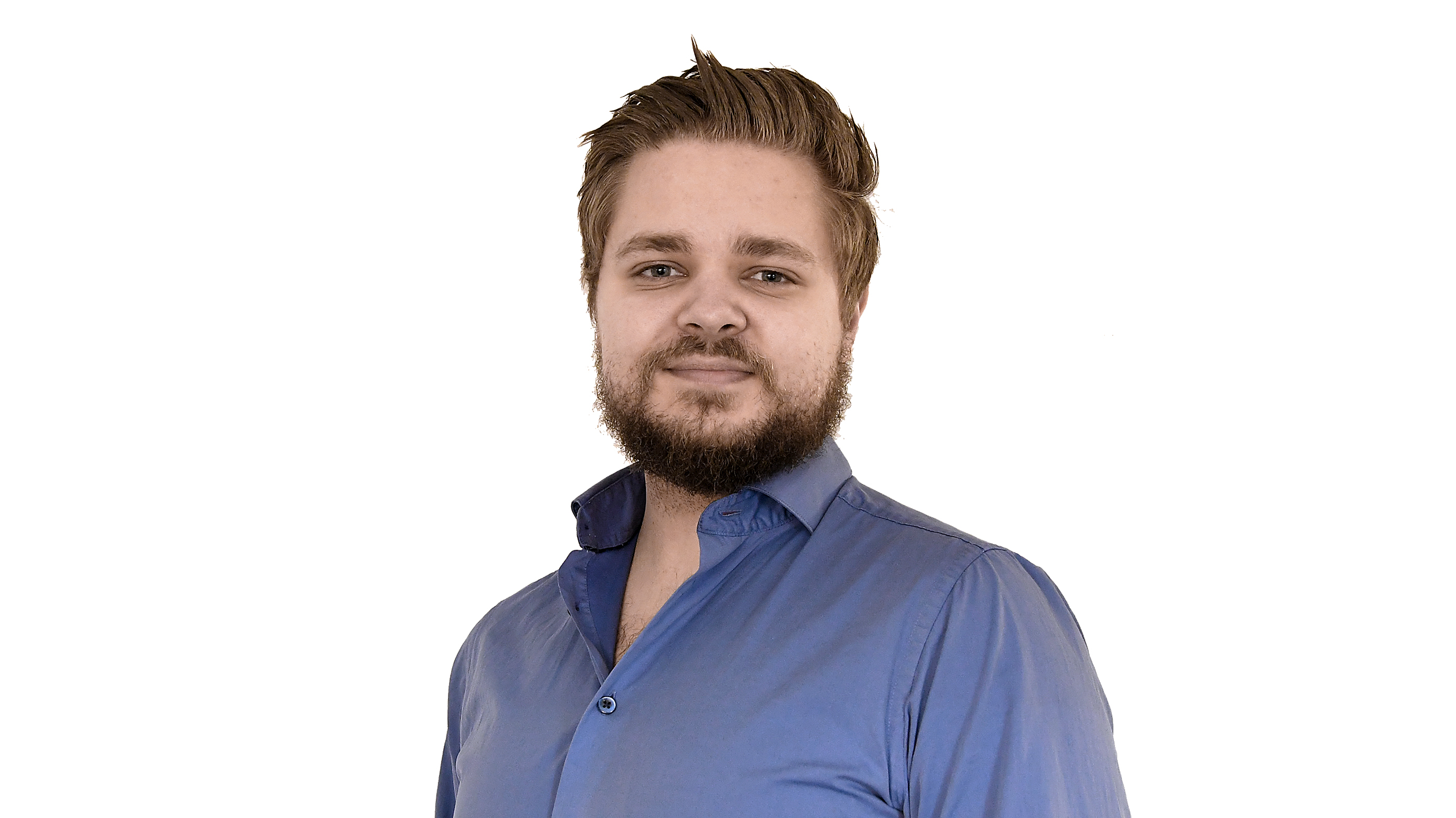 Bilden föreställer en leende man med kort hår och skägg, klädd i blå skjorta.