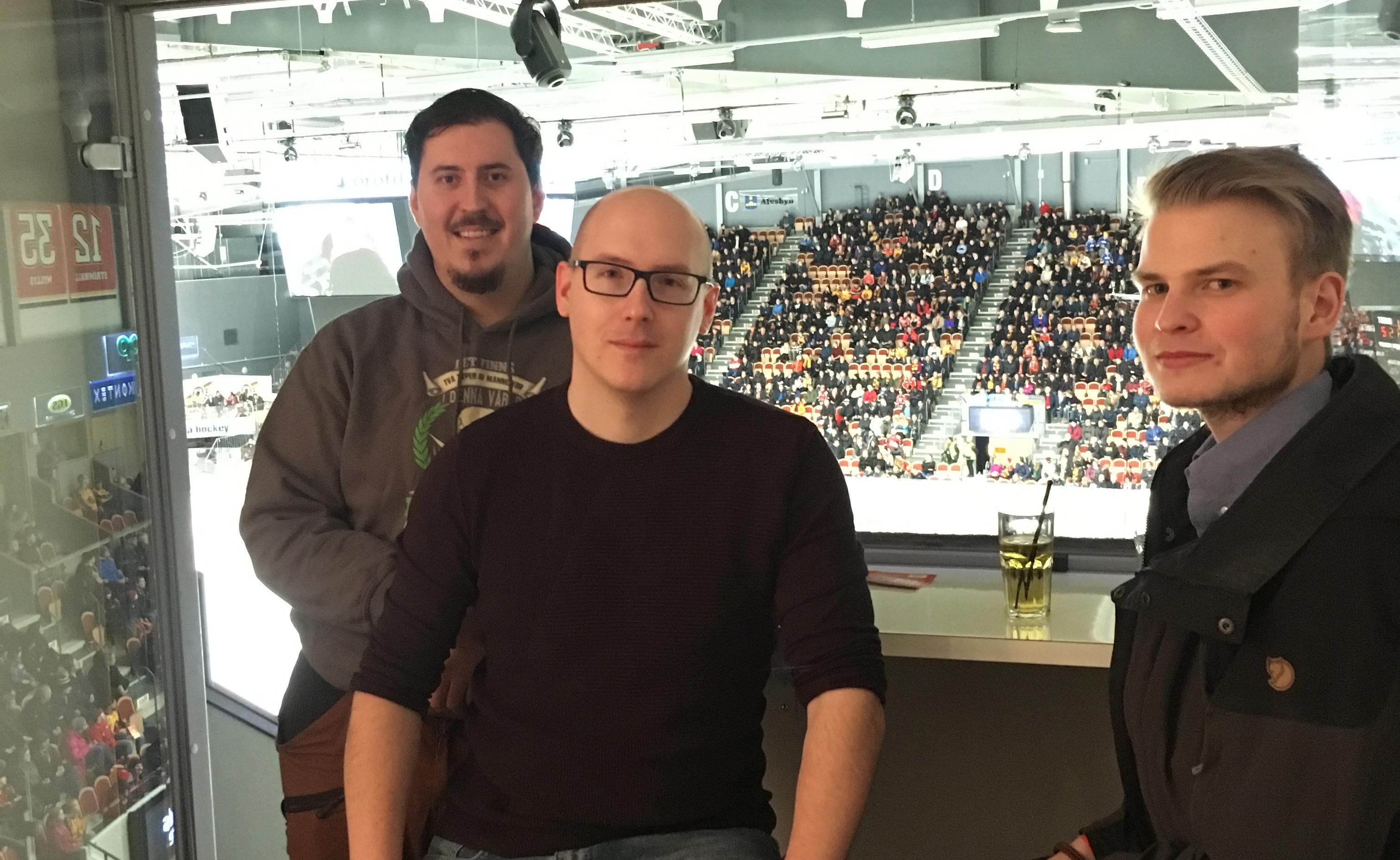 Bilden föreställer tre män som står i en utsiktsloge i en hockeyrink. I bakgrunden syns läktare och publik.