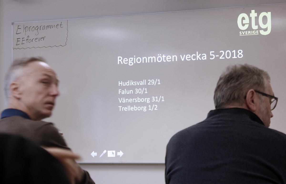 Bilden föreställer en whiteboard där en projektor projicerar upp texten: Regionsmöten vecka 5, 2018. Hudiksvall 29/1, Falun 30/1, Vänersborg 31/1, Trelleborg 1/2. I förgrunden syns två åskådare.