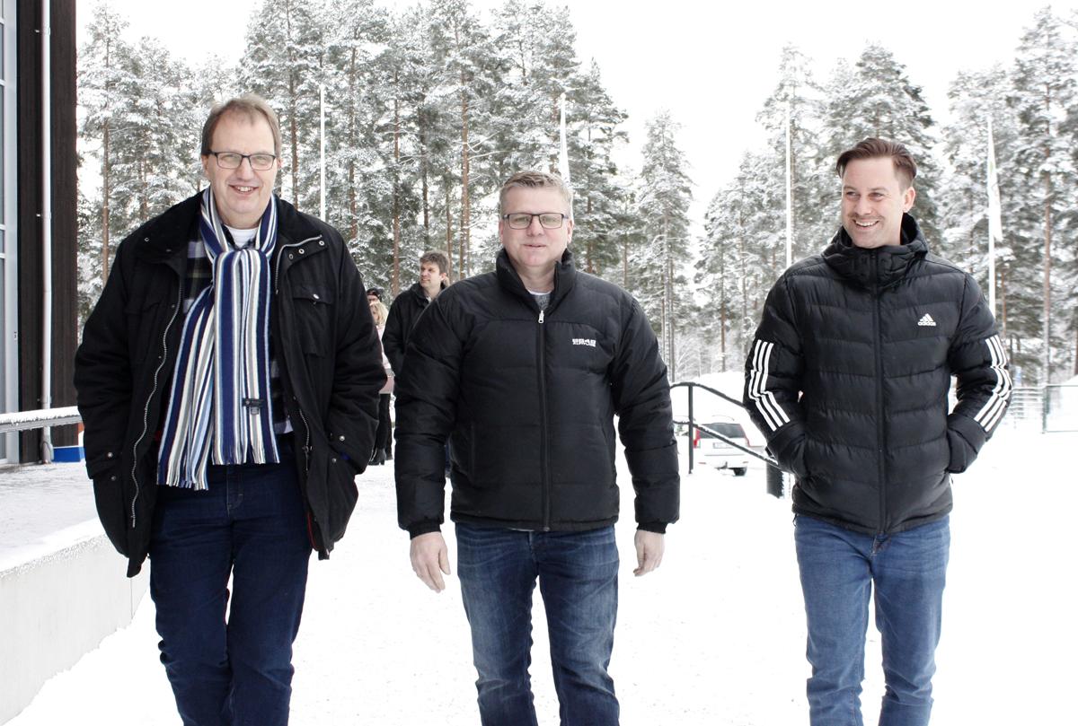 Bilden föreställer tre leende män som går mot kameran i en snötäckt omgivning.
