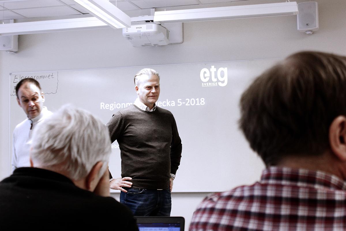 Bilden föreställer en man som står med händerna på höfterna framför en whiteboard där ordet ETG projicerats med hjälp av en projektor. I förgrunden syns ryggarna på två åhörare.