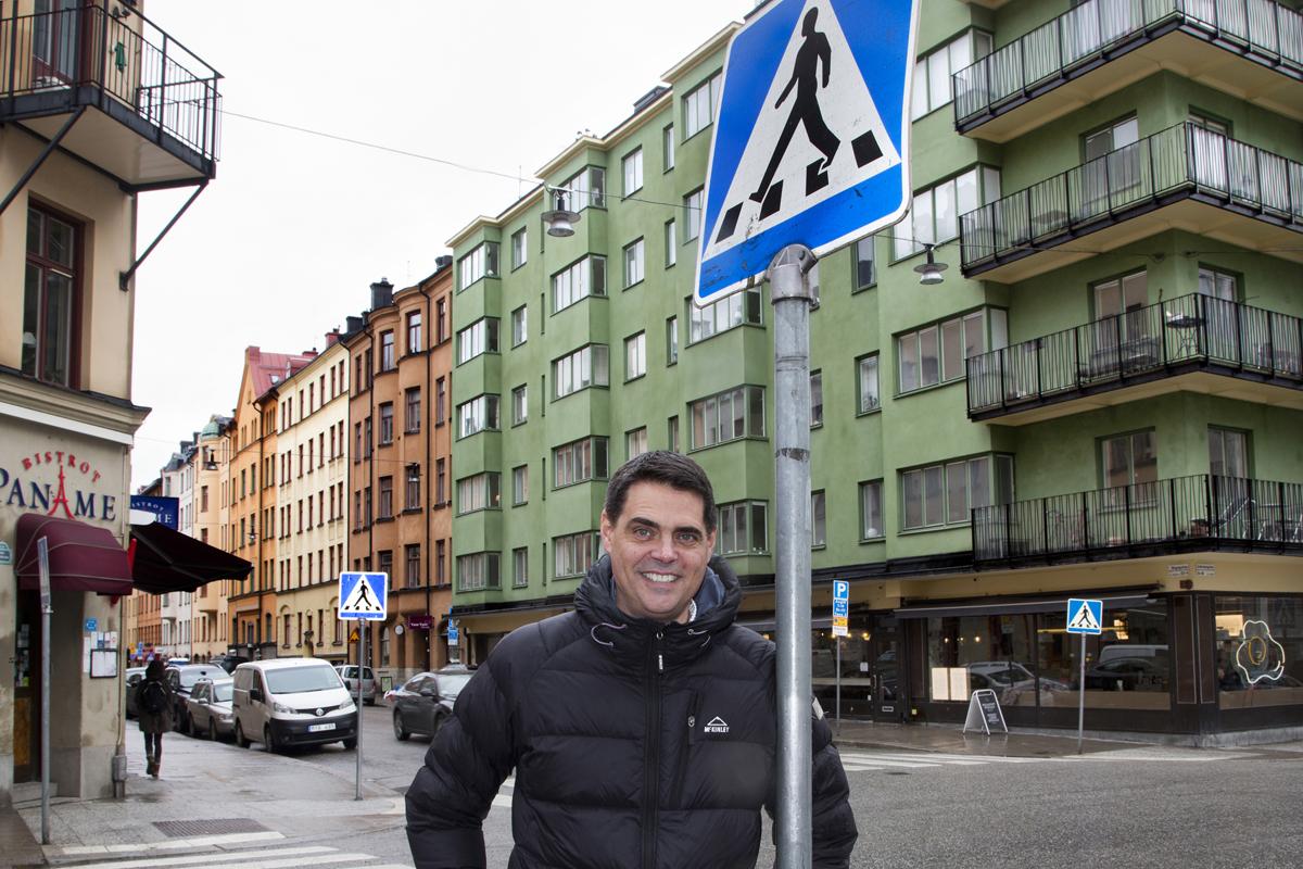 Bilden föreställer en leende man invid en skylt för ett övergångsställe i en vägkorsning.