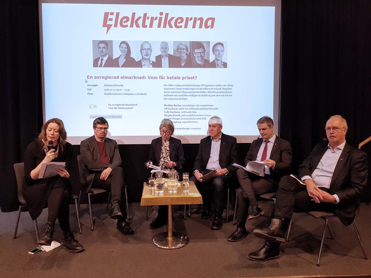 En grupp personer framför en presentation på en stor skärm