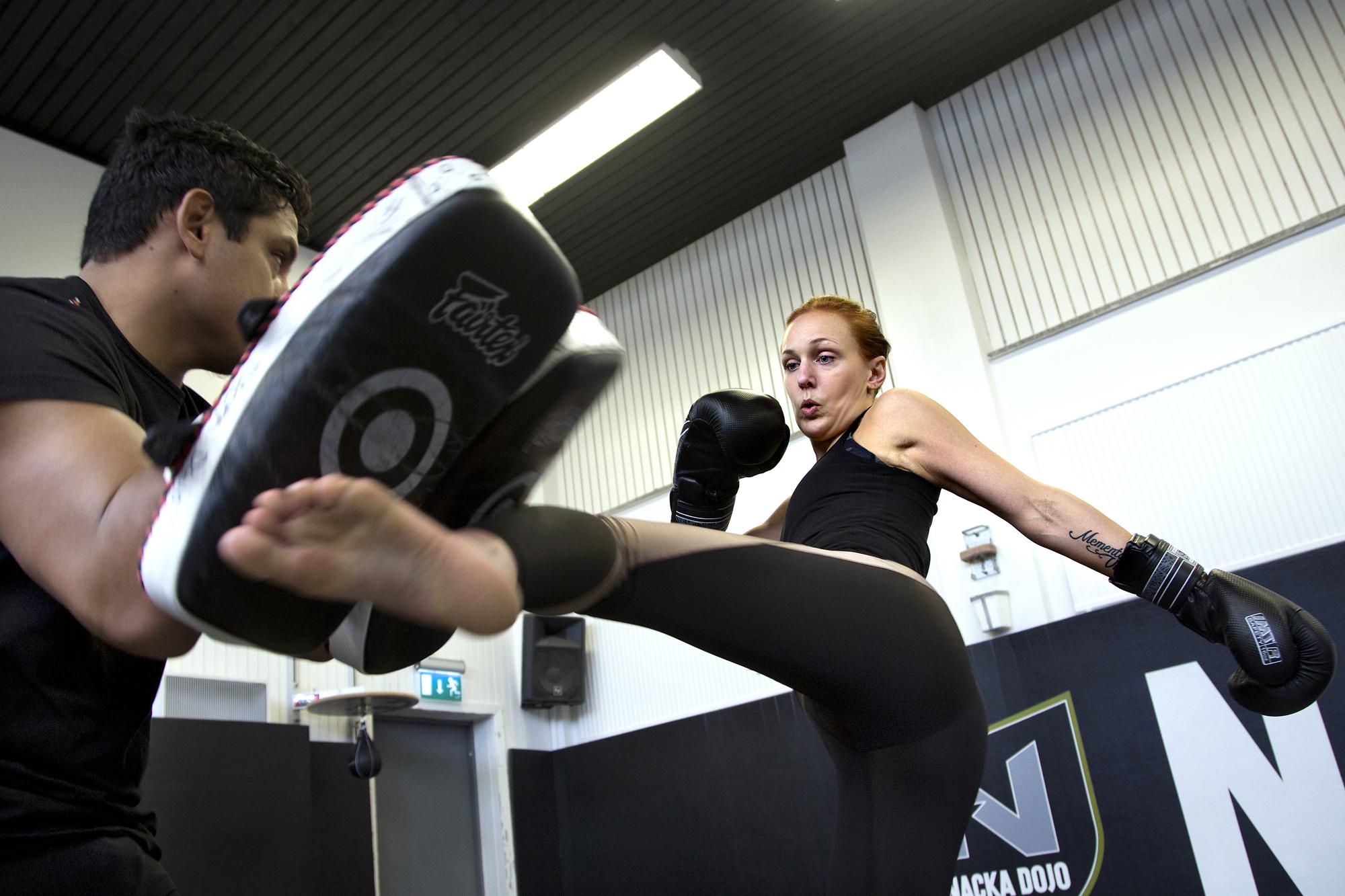 Louise Olsson sparkar mot en träningsplatta i boxningsringen.