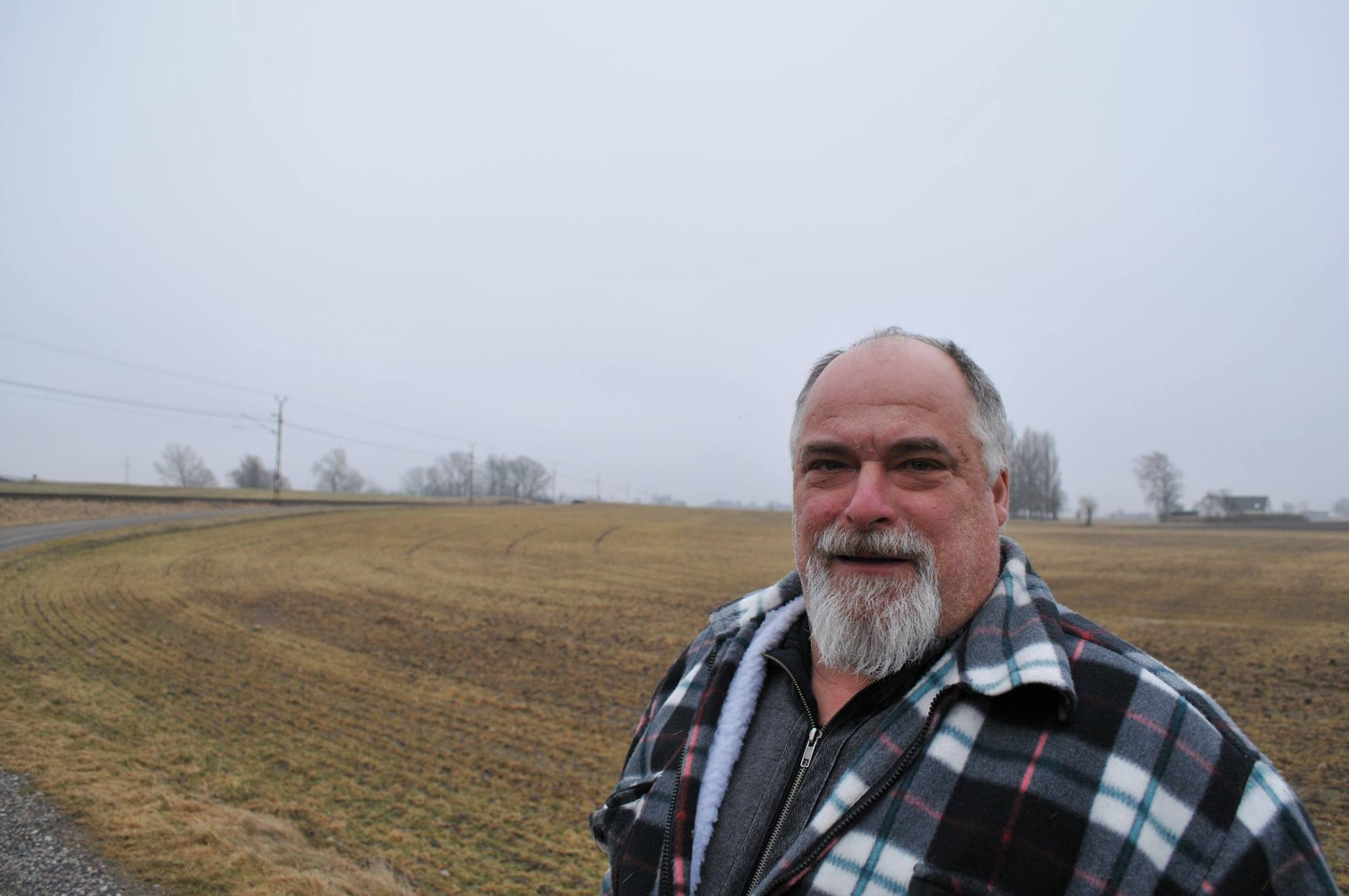 Stefan Pålsson mot en bakgrund av fält och himmel