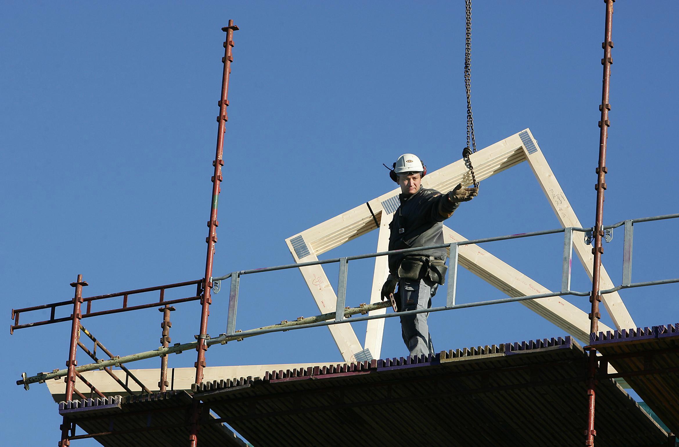 Bilden föreställer en person i vit bygghjälm som står på en byggnadsställni8ng och sträcker ut en hand. Bakom honom syns en träram som lyftas i en kedja.