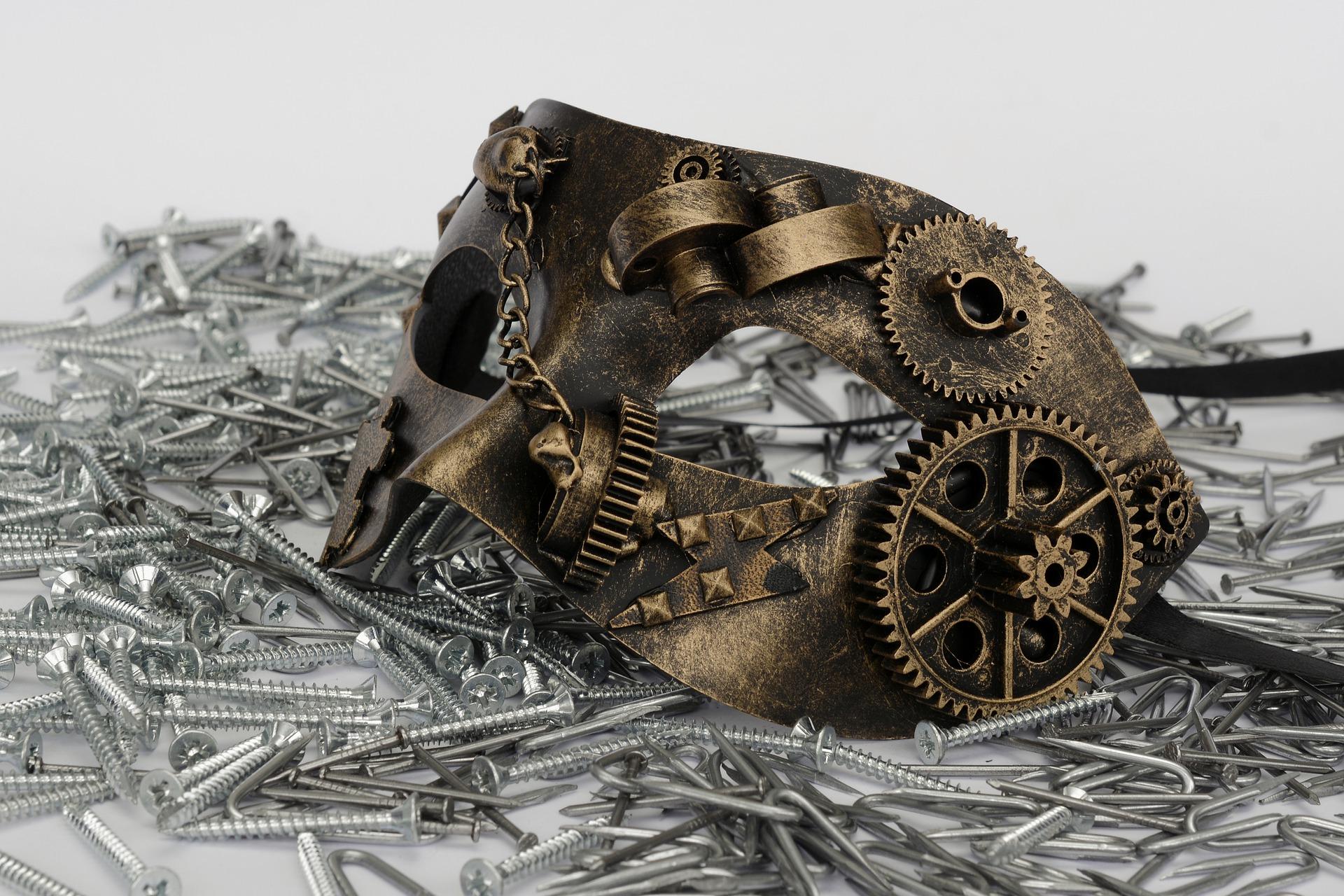 Bilden föreställer en bronsfärgad teatermask som ligger på en massa utspridda skruvar och spikar. Masken har även kugghjul och kedjor på sig.