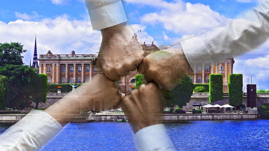 Bilden föreställer riksdagen i Stockholm, omgiven av vatten och gröna träd. Över bilden är fyra skjortklädda armar monterade, vars knutna nävar möts i ett handslag mitt över riksdagsbyggnaden.