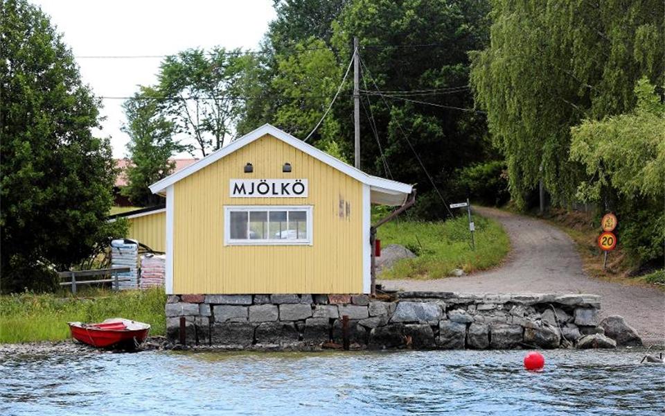 Ett guld hus vid vattnet. På husets skylt står det Mjölkö.