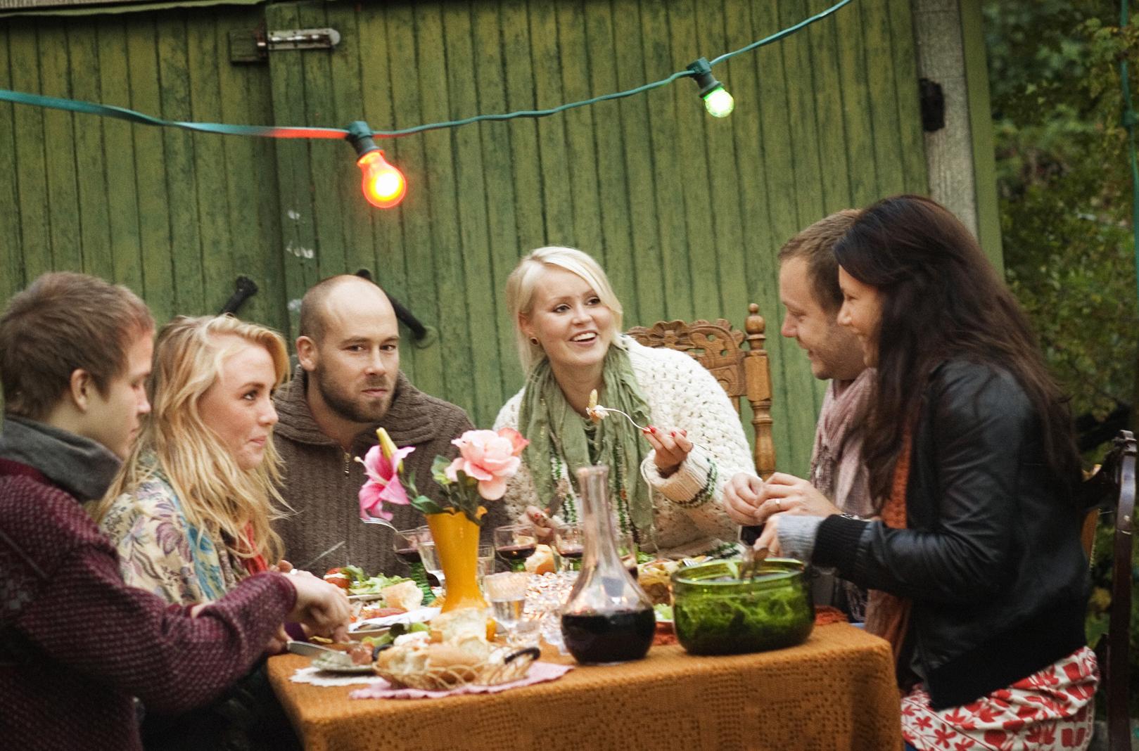 en samling personer runt ett altan-bord med mat på