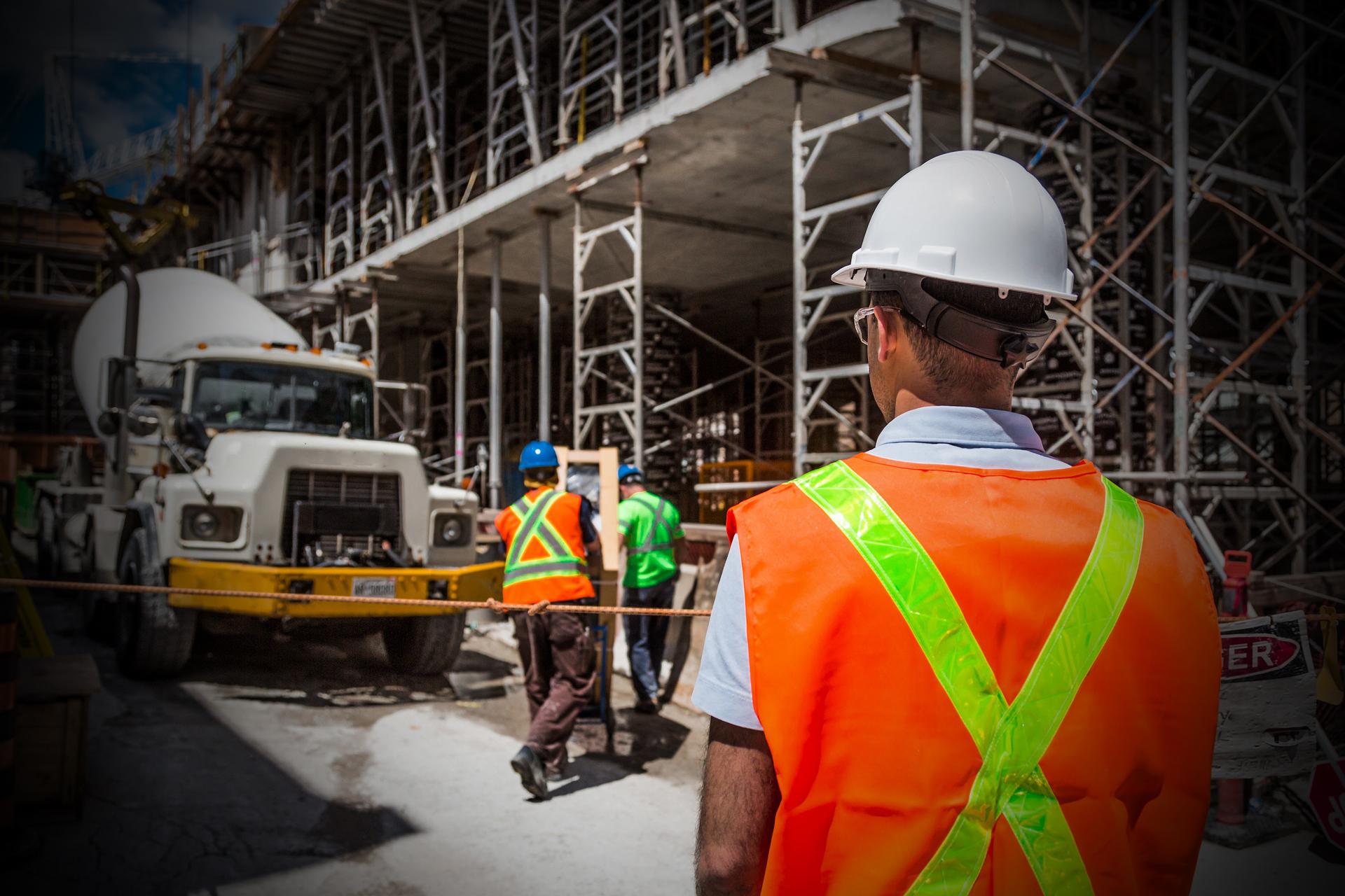En person i reflexkläder och hjälm står och tittar mot ett bygge med byggställningar.