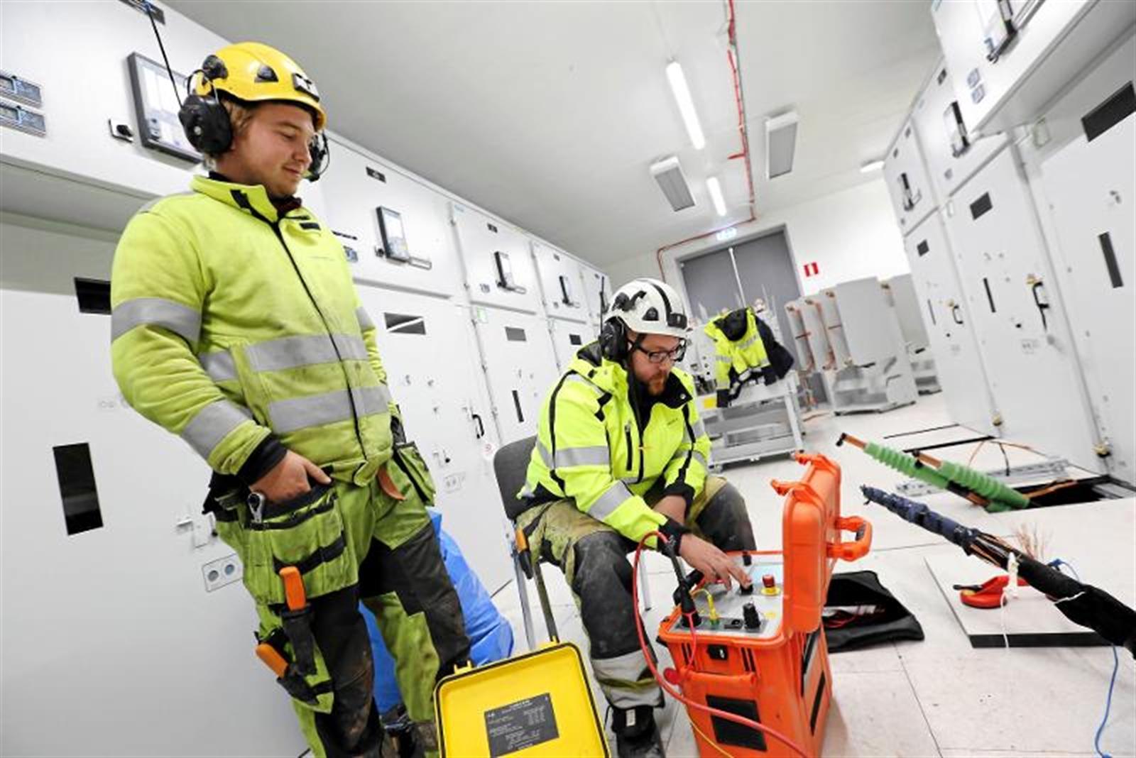 Jonathan Jakobsson och Mikael Mickelsson arbetar med felsökning inne i ett av ställverken.