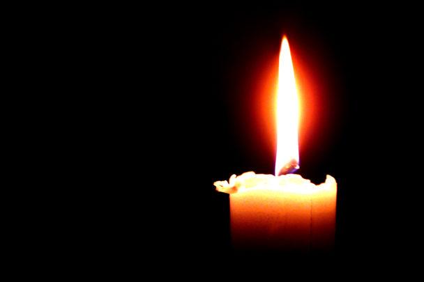 Ett ensamt stearinljus med varm låga.