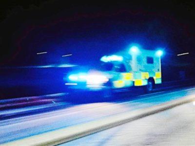 En ambulans med sirener åker på en mörk landsväg