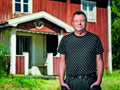 Göran står framför ett rött lantligt hus