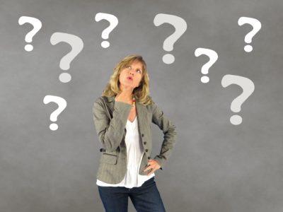 En kvinna står och ser fundersam ut, omgiven av tecknade frågetecken.