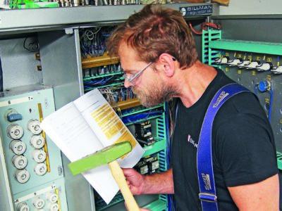 En person står framför ett proppskåp och läser en manual