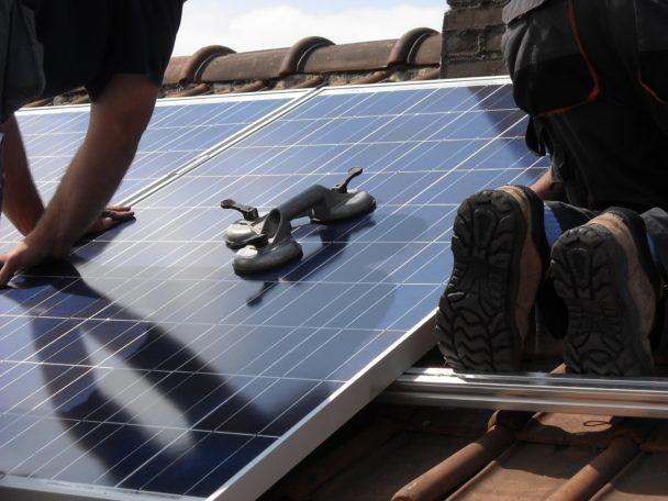 Två personer installerar solceller på ett tak