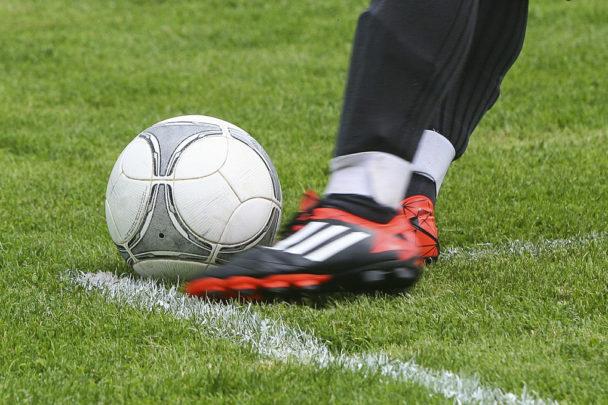 En fot i röd sko sparkar mot en fotboll på en gräsplan.