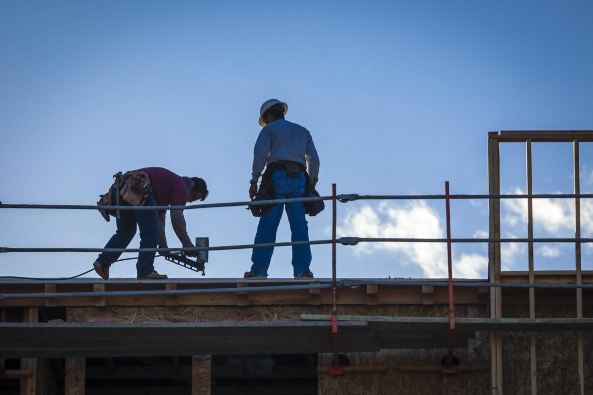 Två byggarbetare på hög höjd mot en blå himmel.