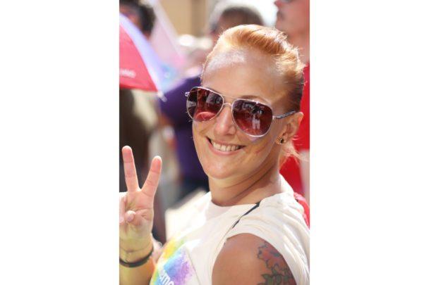 Louise Olsson i solglasögon, som ler och gör peace-tecknet mot kameran.
