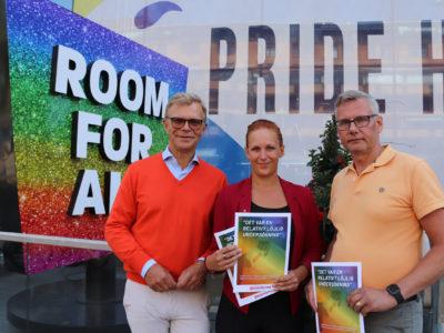 """Ola Månsson, Louise Olsson och Per-Håkan Waern står framför en skylt med texten """"Room for all"""", hållande utskrifter av rapporten i artikeln."""