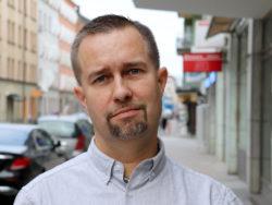Porträttfoto av Tomas Jansson, ombudsman på Elektrikerförbundets förbundskontor, mot en stadsbakgrund.
