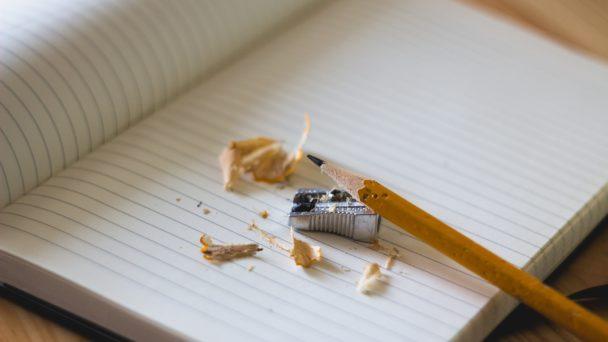 En nyvässad penna och en hög med pennspån på ett skrivblock.