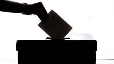Silhuetten av en hand som lägger en röstsedel i en valurna