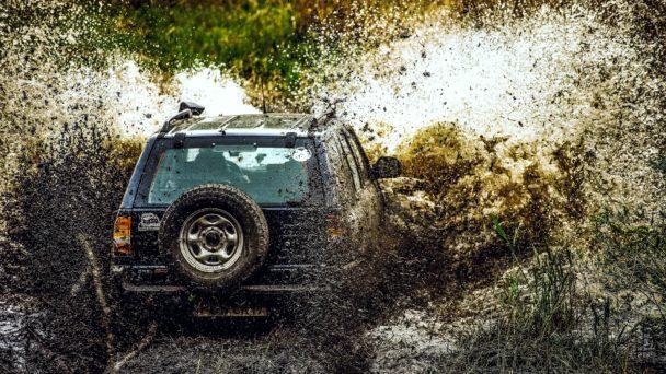 En jeep som kör offroad i en kaskad av lort och lera