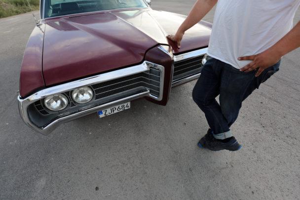 Magnus Pernils står framför sin Pontiac med handen på motorhuven.