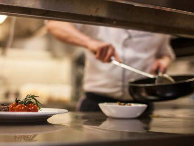 En person står och lagar mat i ett restaurangkök.