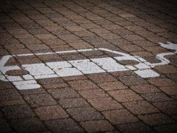 En parkeringsplats med en stiliserad ikon av en elbil målad på marken.