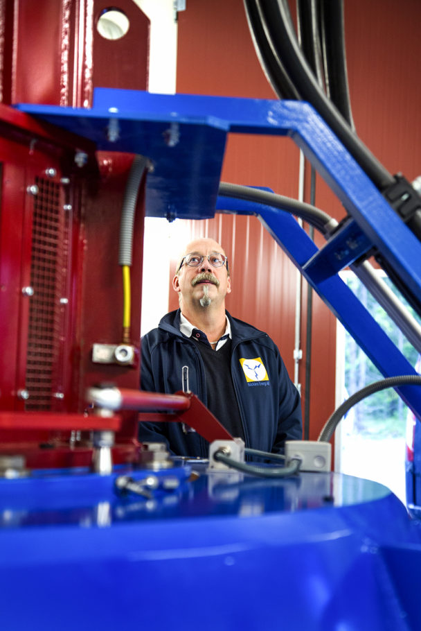 En person står på andra sidan av en blå maskin och tittar uppåt.