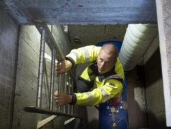 En person i gula reflexkläder klättrar ned för en stege.