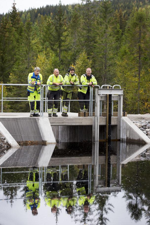 Fyra personer i gula reflexkläder står tillsammans på en kraftverksdamm.