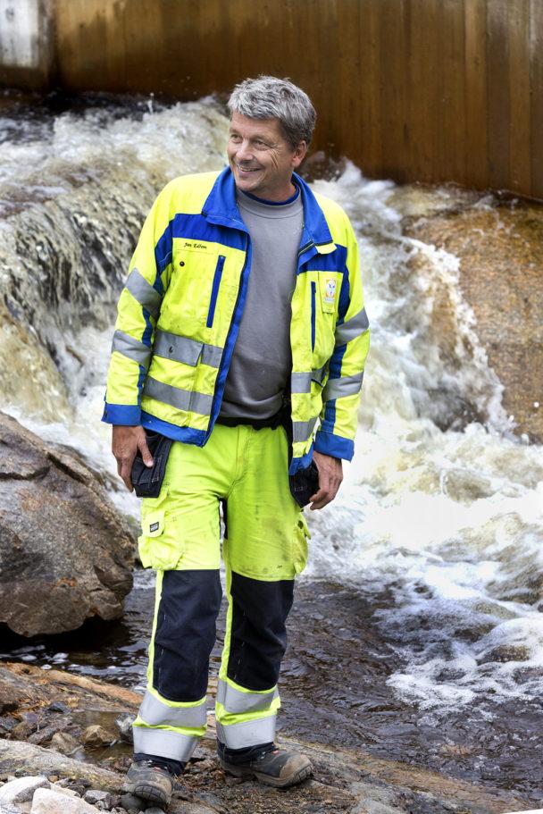 En person i gula reflexkläder står framför ett fall i ett forsande vattendrag.